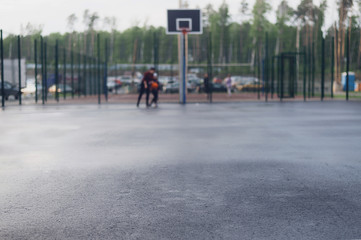 Wet asphalt in focus for text on the background of street basketball court on which people play