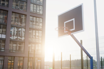 Street basketball court and basketball Hoop on sunset background.