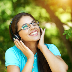 Beautiful girl listening to the music wearing headphones