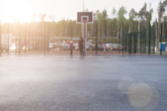 Wet asphalt in focus for text on the background of street basketball court on which people play and which shines the evening sun
