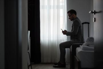 Businessman using smart phone at hotel room