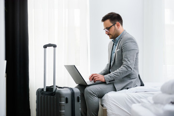 Businessman using laptop computer, working at his hotel room. Traveling for work.