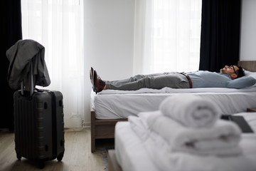 Exhausted businessman laying on bed in hotel room
