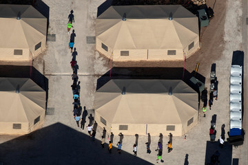 Immigrant children are led by staff in single file between tents at a detention facility in Tornillo, Texas