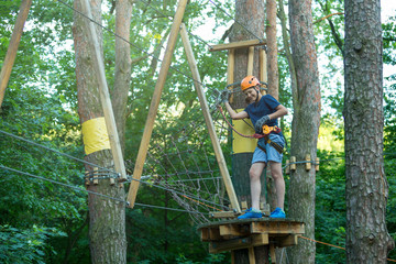 Active sporty kid in helmet doing activity in adventure park with all climbing equipment. Active children climb on the trees and having fun outdoors. Summer camp.