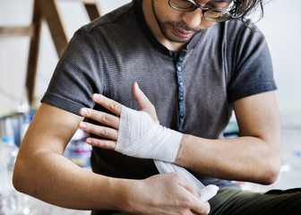 Man wrapping injured hand with bandage