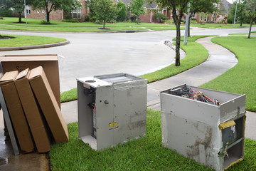 Old gas furnace units sitting at curb after technician has replaced units with new heaters