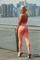 Young beautiful blond fitness model in bright stylish sportswear posing pretty on the pier with city on the background.