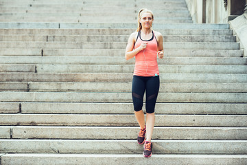 Woman running on steps in New York Central Park listen to music and wearing sport clothes at summer time