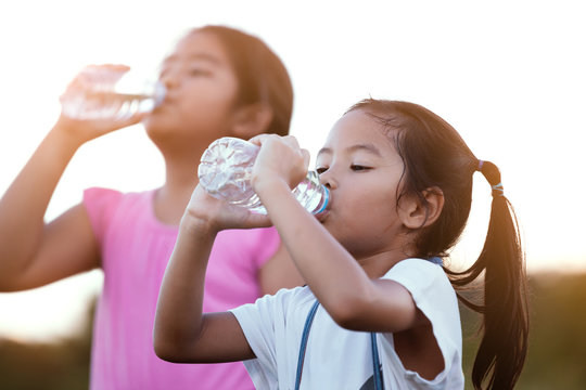 Cute asian little child girl drinking fresh water from bottle with her older sister after exercise together in summer time
