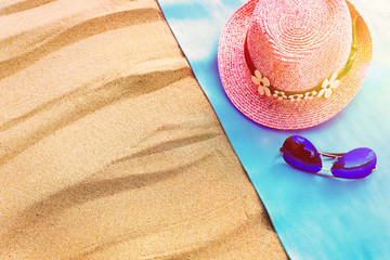 Top view of a sandy beach with a frame of blue towels with a hat and glasses. copy space and visible sand texture.
