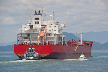 A tanker is assisted by pilot and a tugboat