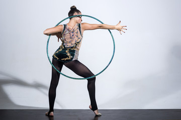 fitness woman dressed in sportswear working with hula hoop over grey.