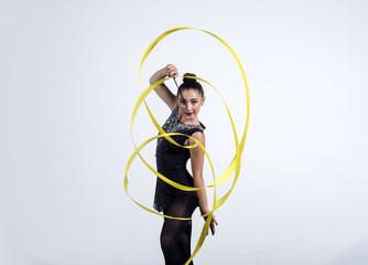 girl train acrobatics with ribbon. girl curl yellow ribbon in rhythmic gymnastics.