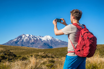 Tourist hiker man taking picture with phone of mountains in New Zealand during hike on Tongariro Alpine crossing track in New Zealand, NZ. Travel tramping lifestyle.