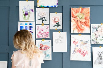 creative art lifestyle. drawing hobby and self expression. painter standing against the wall with her artwork. watercolor drawing assortment