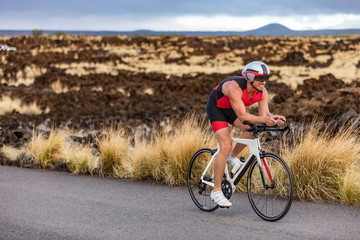 Triathlon professional cyclist man cycling road racing bike in time trial helmet and compression tri suit in Hawaii landscape for Kailua-Kona ironman. Triathlete biking in nature.