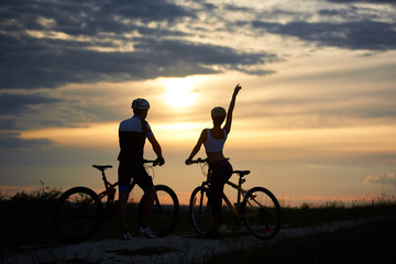 Rear view of a couple of cyclists standing with bicycles and enjoying the sunset. Man and woman are dressed in helmets and sportswear. Perfect sky with clouds and evening sun