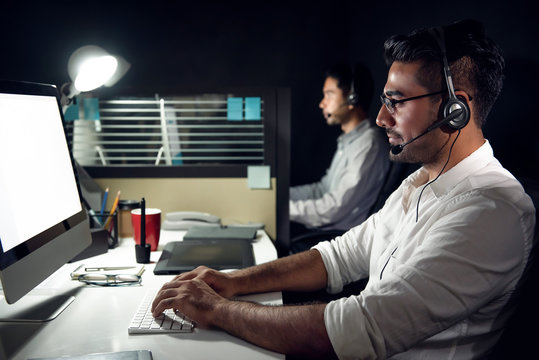 Male Asian customer service  telemarketers working night shift in call center