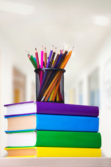 Glass with colored pencils on a stack of books on a table, school concept