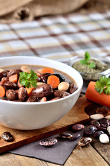 Bowl of bean soup with large beans on cutting board, carrots, parsley, marjoram, spoon and ladle, towel in background - vertical photo