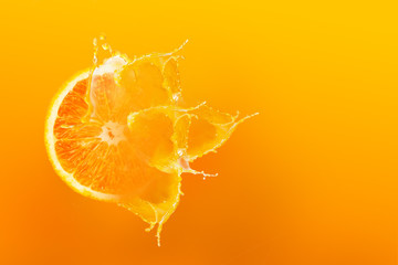 Wall Murals Juice Fresh half slice of ripe orange fruit floation with splash drop on orange juice with copy space