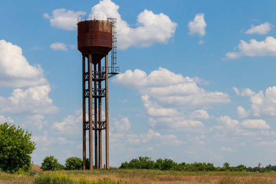 Old rusty water tower in the green field