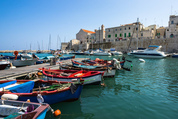 In de dag Blauwe jeans Colorful boats at Giovinazzo harbour with the Cathedral on the background, Apulia, Italy