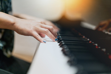 women hand on classic Piano keyboard closeup