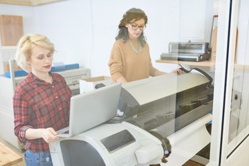 Two lovely women standing in printing office and using laptop and printer.