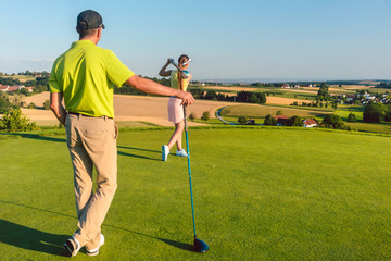 Full length rear view of a man wearing modern golf outfits, while watching his partner striking the ball during match on the green grass of a professional golf course in summer