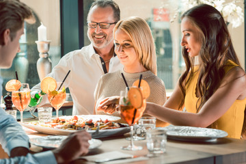 Blond beautiful woman served by an experienced waiter while having lunch with her best friends at a trendy restaurant