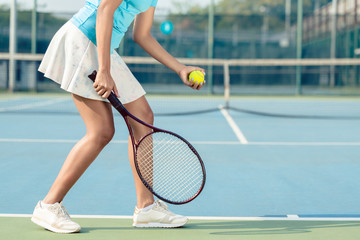 Side view low section of a young woman wearing white skirt and tennis shoes while serving during professional match