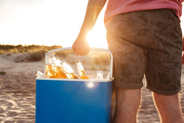 Cropped photo from back of caucasian guy in casual summer outfit carrying ice chest with lots of beer bottlesб during party at seaside