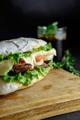big sandwich  on black background rosemary cucumber wooden board Street food, fast food. Homemade burgers with beef, cheese  on the wooden table. Glass of cola with ice, mint