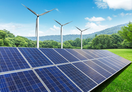 Solar panels and wind turbines in green grass field