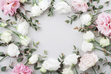 Foto op Canvas Bloemen Beautiful floral frame of pastel flowers and green eucalyptus leaves on gray table top view. Flat lay composition.