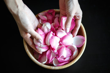 Close-up macro photo of woman's hands with rose petals, wooden bowl on a black table
