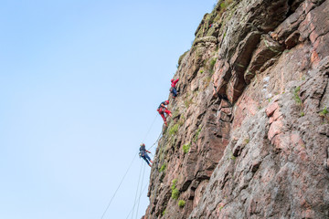 Rock climbing. A group of young rock climbers climb the vertical granite rock. Extreme sport.