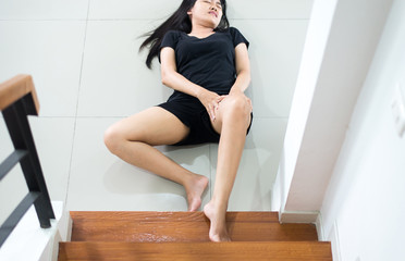 Hands female touching her legs injured,Asian woman falling down of staircase