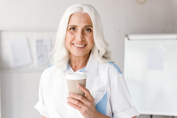 Mature woman indoors in office working drinking coffee