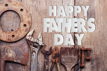 Paper cut of Happy Father's Day text with old rusty tools on wooden background