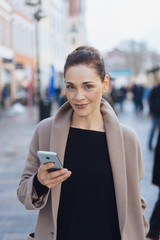 Street portrait of young smiling woman with phone