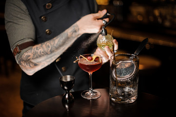 Tattooed bartender spraying on the delicious cocktail with a special liquid