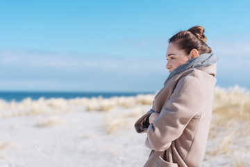 Woman in coat standing at beach on sunny day