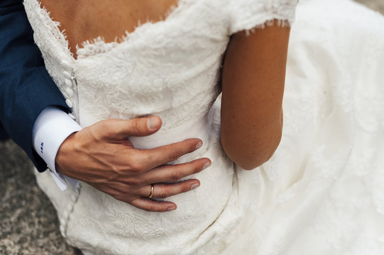 Close up of groom hand embracing brides back