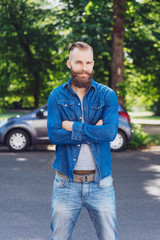 Confident macho bearded man in denims