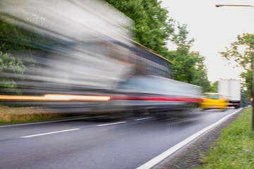 Fotomurales - Trucks and cars hurrying, speeding - blurred motion and lights of the cars, streaks of trails.