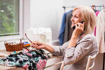 Adult woman is sewing in her studio. She is talking with client.