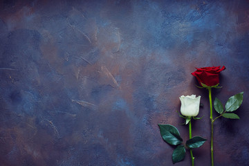 Two roses lie on a stone slab